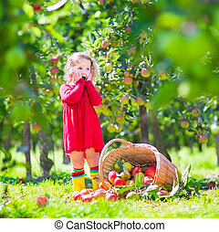 Little girl next to an apple basket tpped on its side -...