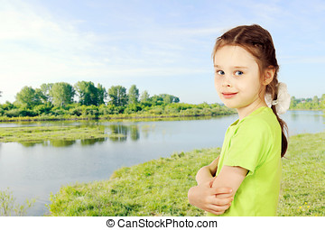 Little girl on a bank of the river in summer