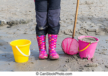 Little girl on a beach with 2 buckets and a net