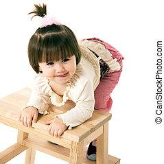 little girl on a chair