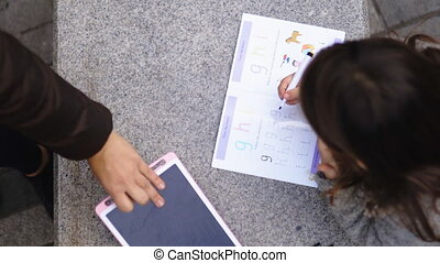 Little brunette girl from above on a concrete bench using a book to learn how to write. Young child learning to write and read. Homeschooled children