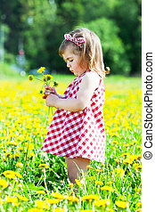 little girl on a glade with dandelions