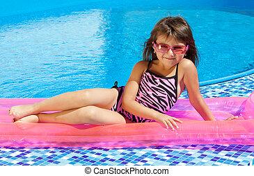 little girl on a pink mattress