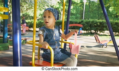 Little girl on a playground. Child playing outdoors in summer. Children having fun at daycare play ground.