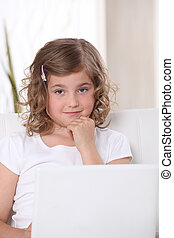 Little girl on a sofa with laptop