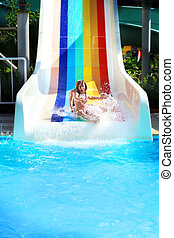 Little girl on a waterslide in aquapark. - Funny photo of...