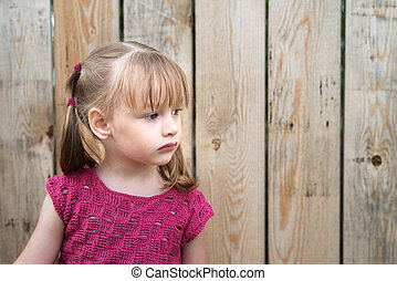 Little girl on a wooden fence background