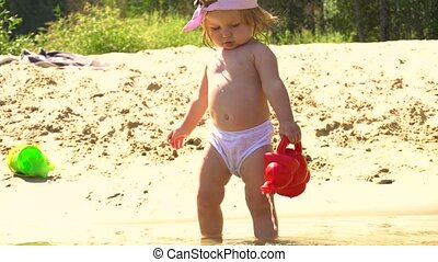 Little girl on beach playing with watering pot