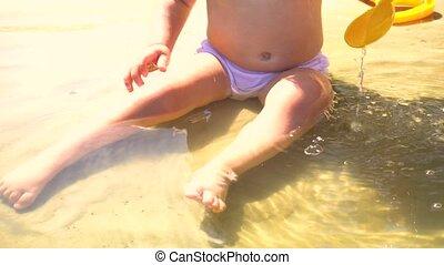 Little girl on beach sitting in water - Little girl in...