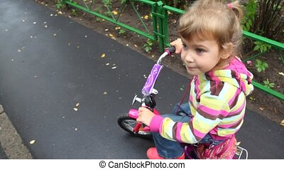 little girl on bicycle talking and then riding from camera