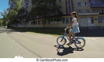 Little girl on blue bike - Happy child riding a bike in...