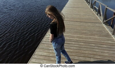 Little girl on floating bridge in lake