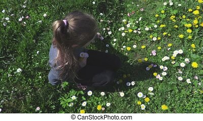 Little girl on grass near flowers