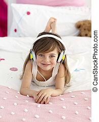 Little girl on headphones listening to the music