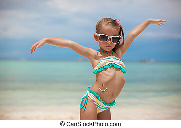 Little girl on her stomach painted a smile by sun cream -...