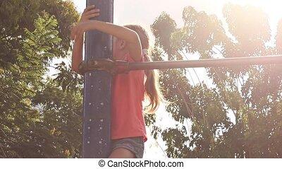 little girl on horizontal bar in park outdoors - little girl...