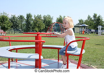 Little girl on merrygoround - Little girl playing on the...
