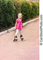 Little girl on roller skates at park