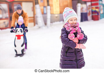 Little girl on skating rink, dad with little sister in the background