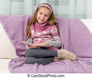 little girl on sofa with the book - little cute girl on sofa...