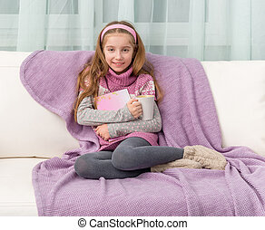 little girl on sofa with the book