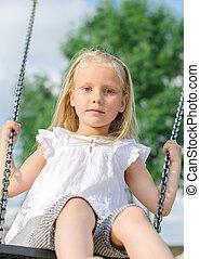 Little girl on swing in the park