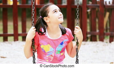 Little girl on swing smiling
