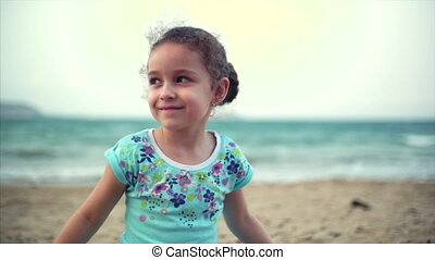 Little girl on the beach, happy little baby playing with sand on the beach. A child, a child, children, emotions.