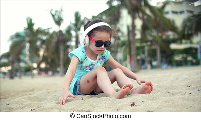Little girl on the beach wearing sunglasses, listening to music in white headphones and playing with sand on the beach. Child, children, emotions.