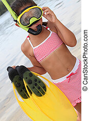 little girl on the beach wearing swimsuit and having diving apparatus