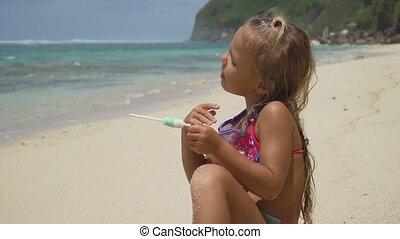 Little girl on the beach with a lollipop.