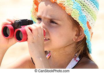 Little girl on the beach with binoculars