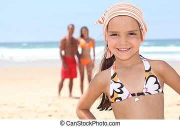 Little girl on the beach with her parents