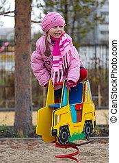 Little girl on the carousel in the autumn