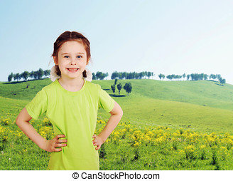 Little girl on the green meadow in sunny day
