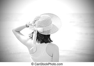 little girl on the seashore with hat and light tones