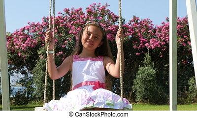 Little girl on the swings - Adorable little girl in white...