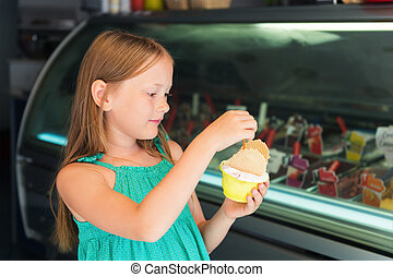 Little girl on vacation, kid girl buying ice cream in the shop