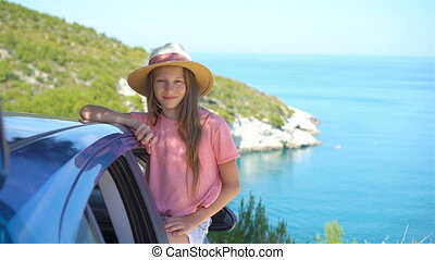 Little girl on vacation travel by car background beautiful...