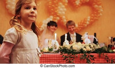 little girl on wedding, behind groom with bride behind table...
