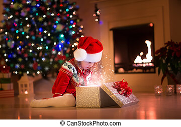 Little girl opening Christmas presents next to a fire place