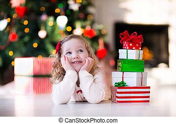 Little girl opening presents on Christmas morning - Family ...