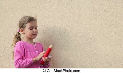 Little girl opens cap of big pencil and write on wall