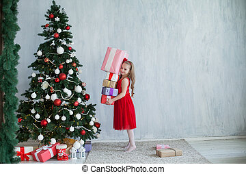little girl opens Christmas gifts at the Christmas tree new year holiday house