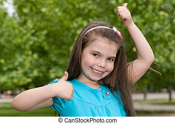 Little girl outdoor with her thumbs up