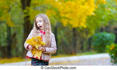 Little girl outdoors at beautiful fall day playing with leaves