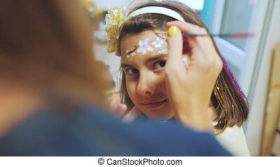 little girl paint on face painting drawing paints. preparing...