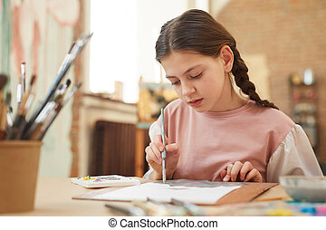 Little girl painting at the table