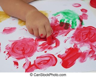 Little girl painting by finger hand paint color ,unlimited boundless imagination through Colorful coloring posters blended on a holiday desk that does not go to school. children development concept.