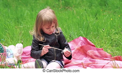 Little girl painting egg and smiling on a lawn in the park. Slowly